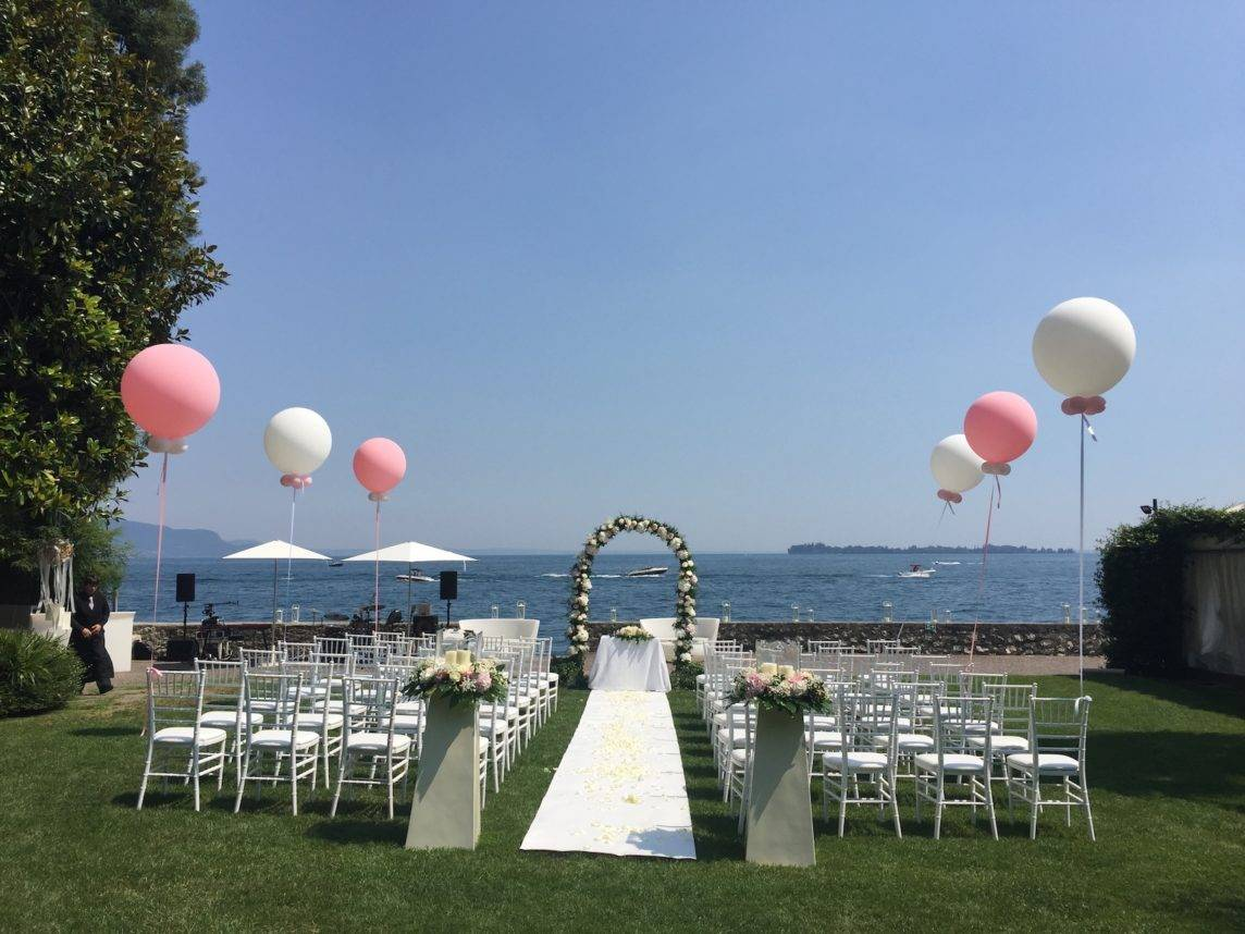 Wedding ceremony set up with white carpet and floral arch. Facing Lake Garda
